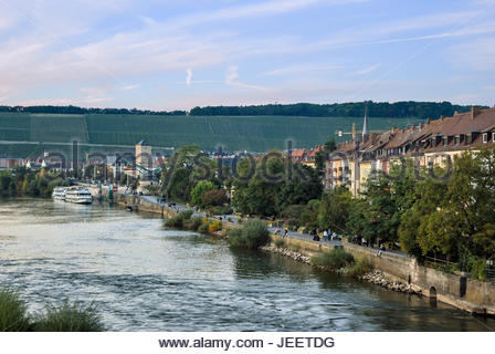 Pedestrians stroll and cruise ships are moored beside the Main River in Würzburg, Germany. - Stock Image