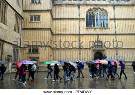 Wet weather - Tourists pass through the courtyard of The Bodleian Library of Oxford University, city of Oxford, UK. - Stock Image