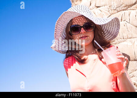 Young girl drinks cold cocktail on the beach - Stock Image