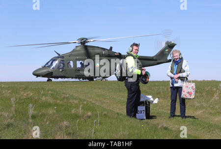 Presiding Officer Carmel McBride and Garda Adrian McGettigan with a ballot box from the polling station to an Irish Air Corp helicopter on the island of Inishbofin. Voters on the remote isle off the coast of Donegal were among the first to cast their ballots in the local and European election, a day ahead of the rest of the country. - Stock Image