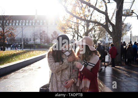 UK, London, two happy women in the city on the go - Stock Image