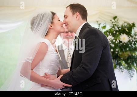 Newlywed couple kissing in wedding - Stock Image