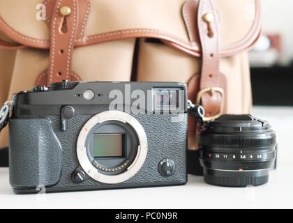 Fuji Mirrorless system camera with sensor visible, with lens and billingham camera bag - Stock Image