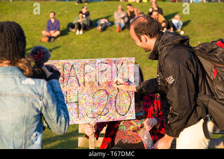VANCOUVER, BC, CANADA - APR 20, 2019: A man giving his signature to a pro marijuana sign at the 420 festival in Vancouver. - Stock Image