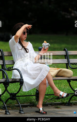 NEW YORK, NY - JULY 10: Young asian woman eats a snack on a hot summer day in Washington Square Park in Manhattan on JULY 10th, 2017 in New York, USA. - Stock Image