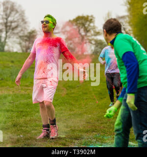 Adult male runner with arms outstretched being covered in paint on Macmillan cancer charity 5K colour fun run. - Stock Image