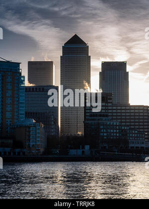 London, England, UK - March 11, 2011: Skyscrapers of the Canary Wharf business district are silhouetted against the sunrise in East London. - Stock Image