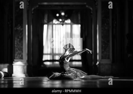 Beautiful ballerina dancing in a hall against the window. Black and white image. - Stock Image