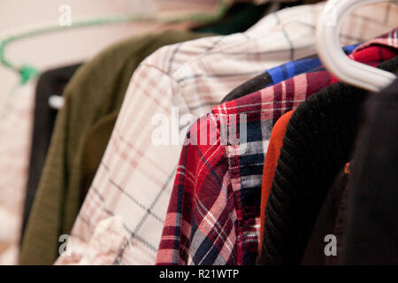 Shoulders and sleeves of shirts on hangers in a closet - Stock Image