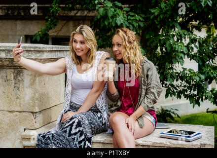 Two female university students sitting together on the campus taking a self-portrait with their smart phone; Edmonton, Alberta, Canada - Stock Image