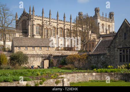 A gardener with a wheelbarrow attends to the Christ Church War memorial Garden with Christ Church Cathedral behind - Stock Image