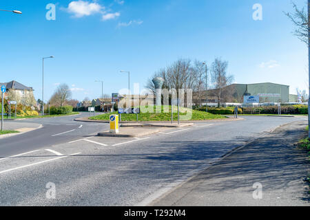 Sculpture of bronze age axe head in the centre of a road traffic roundabout junction at Old Sarum near Salisbury UK - Stock Image