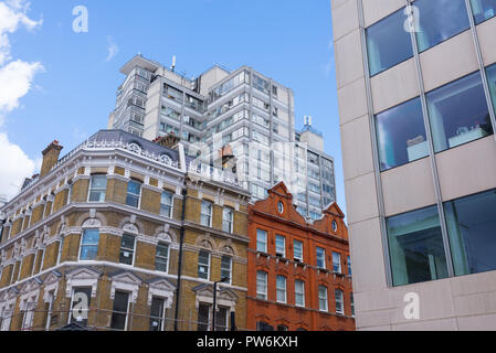 High rise block modern buildings mixed with old restored Victorian residential houses. Modern old architecture mix. - Stock Image