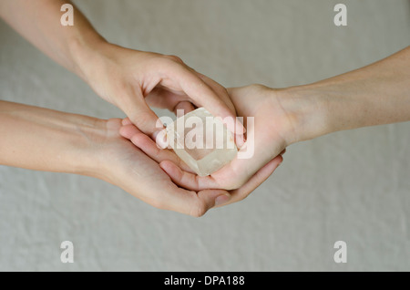 Womans hands holding and placing a quartz crystal in another womans hands in healing gesture. - Stock Image
