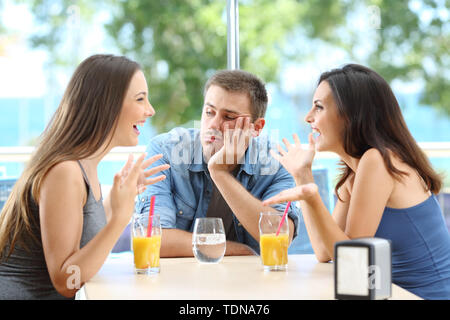 Bored man listening his friends conversation in a coffee shop or hotel on the beach - Stock Image