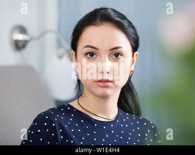 Portrait of stylish young brunette woman at home - Stock Image