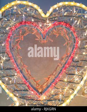 Illuminated heart shape made of electric lamps - Stock Image