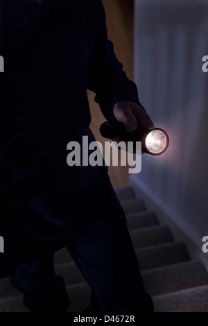Shadowy male intruder holding a torch or flash light - Stock Image