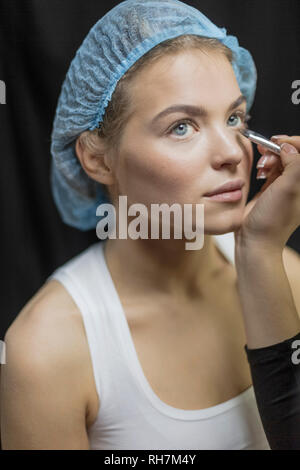 Makeup artist applying makeup to eyes of young woman in shower cap - Stock Image
