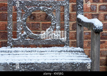 Garden bench covered with dusting of snow, December, England, UK - Stock Image