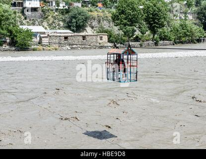 Steel gondola used to cross the river Kunar in Chitral. Operated from the far bank by a hand-powered winch. - Stock Image
