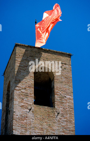 Red flag flying over the city tower of the dramatic hilltop town Sarnano in Le Marche ,Italy - Stock Image