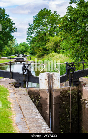 Detail of a lock gate with a flight of locks in the background on the Tardebigge Locks, Worcester and Birmingham Canal, Worcestershire - Stock Image