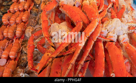 Crustaceans on ice, pile of seafood such as king crabs, shrimps, and lobsters, a local delicacy display, at the famous fish market in Bergen, Norway - Stock Image