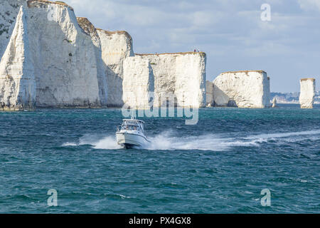 Speed  boat at Old Harry chalk cliffs on Jurassic coast, Dorset. - Stock Image