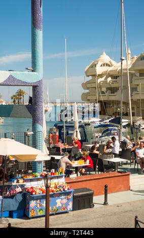 Benalmadena Spain. People sitting at terrace in Puerto Marina, Benalmádena port. Costa del Sol, Málaga province. Andalusia, Southern Spain, Europe. - Stock Image