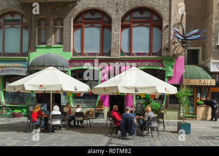Wroclaw, view of people relaxing at tables outside the colorful and quirky Art Cafe and Bar Kalambur in the University Quarter of Wroclaw, Poland. - Stock Image