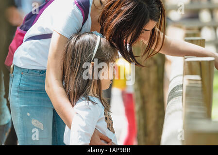 Young mom shows animal or something to her little daughter in zoo.Happy mother and daughter moments with love and natural emotion.Photo of young mothe - Stock Image