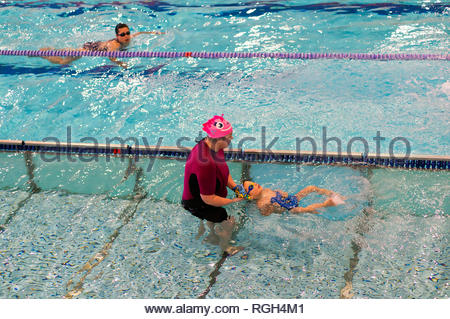 Poznan, Poland - January 26, 2019: Woman assisting boy swimming on his back in a pool during swim lessons in the Termy Maltanskie. - Stock Image
