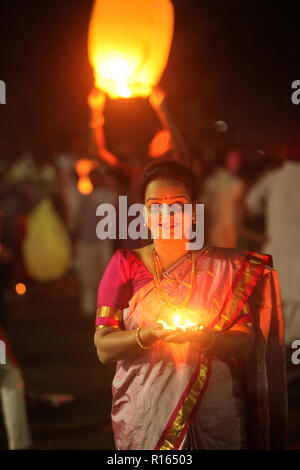 Pune, India - November 2018: A woman lights up a lamp during a public celebration of Diwali festival before sunrise, in India. - Stock Image
