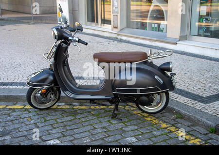 classic motor scooter parked in a cobbled european street - Stock Image