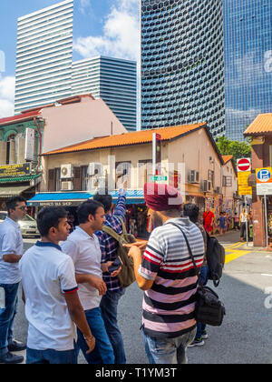 DUO and Gateway office towers over Arab Street traditional shophouses Sikh Indian tourists  Kampong Glam Singapore. - Stock Image