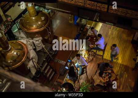 A top view of the ground floor with the beer tanks in Toits Brewpub in Bangalore, India. - Stock Image