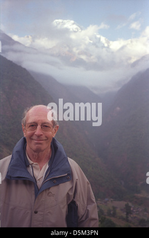 Trekker David Keith Jones with misty view of Modi Khola Valley from Chomrong on Annapurna circuit with snow peaks - Stock Image
