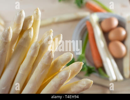 New harvest of white asparagus, high quality raw asparagus, carrot and selery in spring season, ready to cook close up - Stock Image