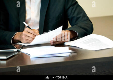 Businessman checking a document on his desk - Stock Image