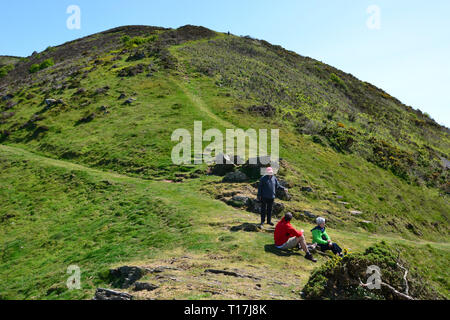 Walkers having a rest on a hilly route along the coast, having walked up from Heddon Valley, Devon, UK - Stock Image