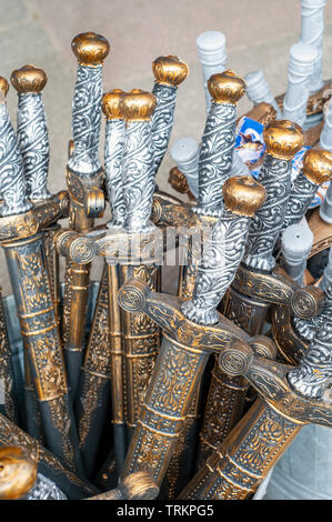 Toy plastic swords on sale outside a shop in Tintagel, Cornwall, UK - Stock Image