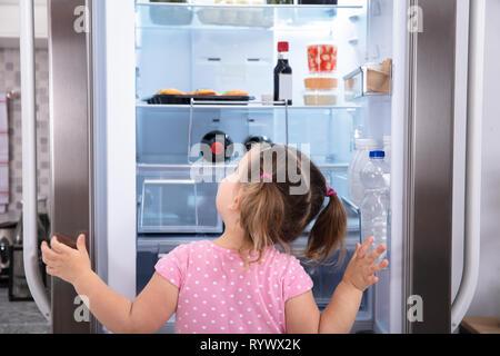 Rear View Of Girl Standing In Kitchen Opening Fridge Door Looking Inside - Stock Image