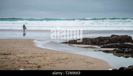A surfer approaching the sea at Trebarwith Strand, North Cornwall, with rough waves and surf. - Stock Image