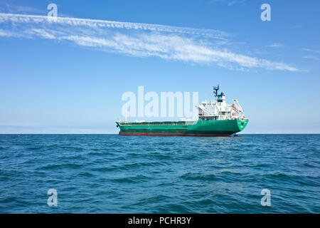 Large green Cargo ship at. Anchor sea open water - Stock Image