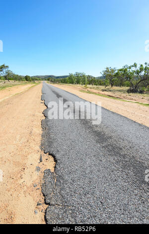 Part of the Savannah Way is a narrow ribbon road with damaged edges, Queensland, QLD, Australia - Stock Image