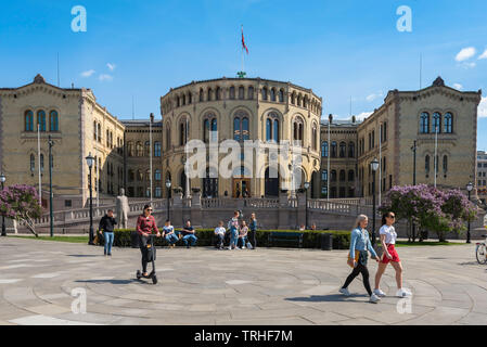 Oslo Norway, view in summer of young people walking past the Norwegian Parliament Building (Stortinget) in Oslo city center, Norway. - Stock Image