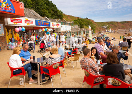 UK, England, Yorkshire, Filey, visitors at Coble Landing cafe tables in sunshine - Stock Image