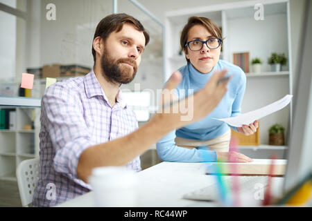 One of young economists or brokers pointing at computer screen while showing his colleague rate changes on website - Stock Image