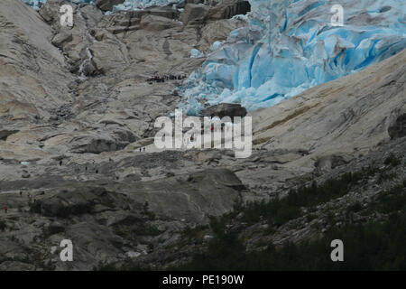 Nigardsbreeen, Norway - 7 August 2018: Tourist see on an excursion of the arm of the Nigardsbreeen Glacier. The glacier highly eroded by the hot 2018 summer is about an hours drive from Skjolden. Photo: David Mbiyu - Stock Image
